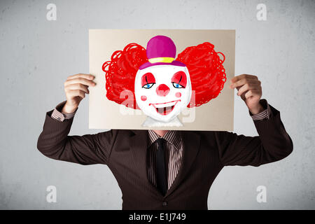 Businessman holding a cardboard with a clown on it in front of his head - Stock Photo