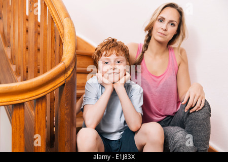 Portrait of mother and son sitting on stairs of their house - Stock Photo