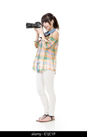 Asian woman takes pictures with photo camera - Stock Photo
