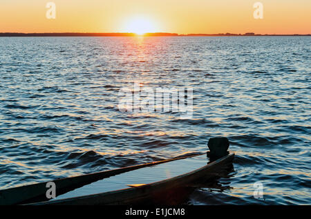 Sunset and drowned boat on summer lake bank - Stock Photo