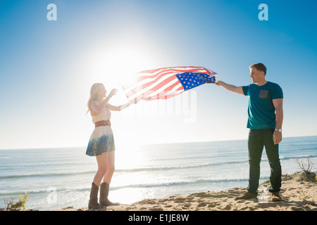 Young couple at coast holding up american flag, Torrey Pines, San Diego, California, USA - Stock Photo