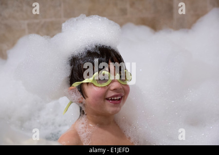 Portrait of young boy wearing goggles in bubble bath - Stock Photo