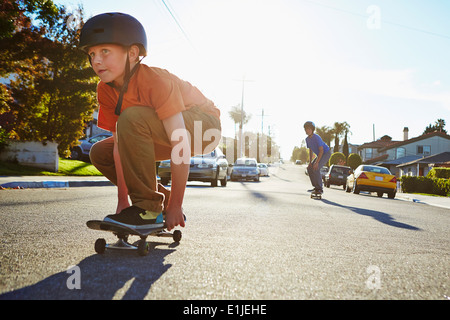 Two boys skateboarding on suburban road - Stock Photo