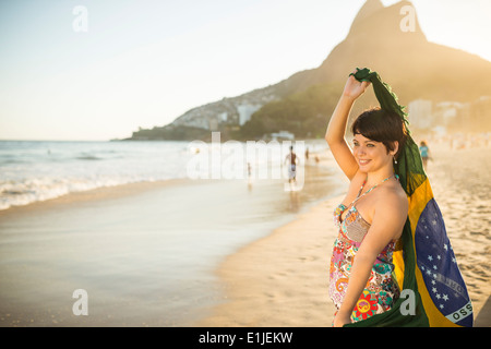 Young woman holding up Brazilian flag, Ipanema Beach, Rio, Brazil - Stock Photo
