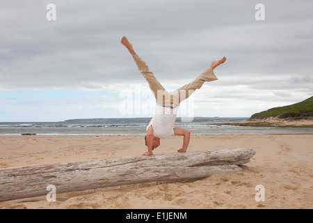 Young man doing handstand on tree trunk at beach - Stock Photo