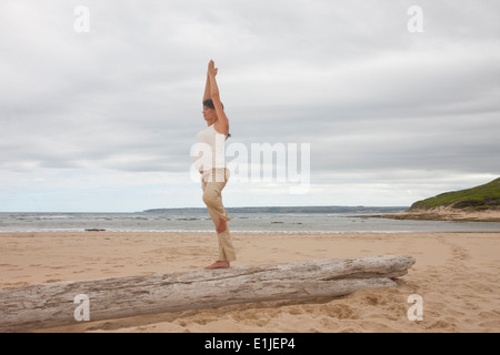 Pregnant mid adult woman practicing yoga on tree trunk at beach - Stock Photo