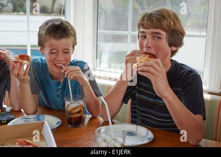 Boys eating pizza - Stock Photo
