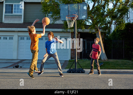 Boys playing basketball outside house - Stock Photo