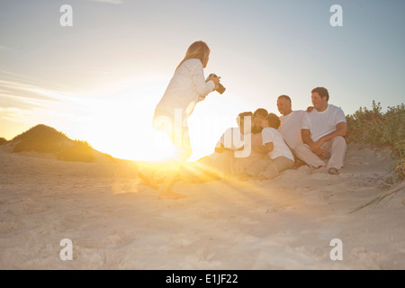 Photographer taking family portrait on beach, Cape Town, South Africa - Stock Photo