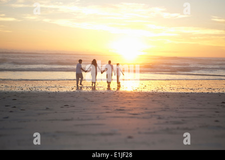 Family holding hands on beach, Cape Town, South Africa - Stock Photo
