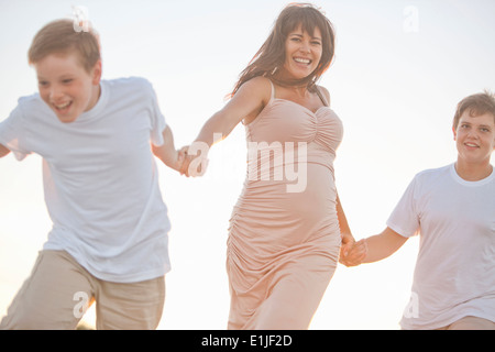 Mother and two sons, holding hands, outdoors - Stock Photo