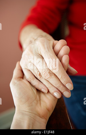 Close up of mature woman holding 82 year old grandmothers hand - Stock Photo