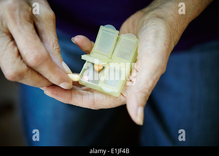 Close up of 82 year old senior woman's hand with pill box - Stock Photo