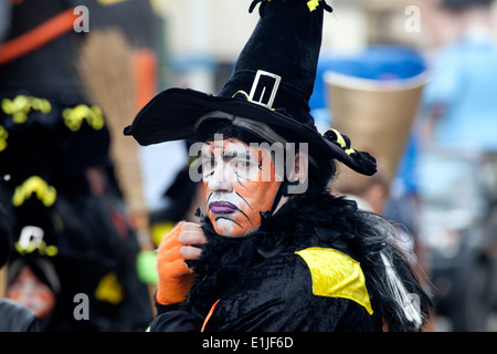 Man parading in traditional witch costume and orange colour face paint, Ostend Carnival, Belgium - Stock Photo