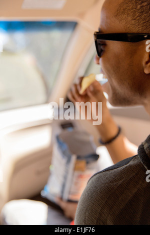 Close up of young man reading snacking on crisps in car - Stock Photo