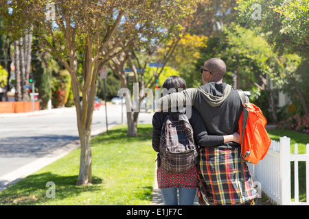 Young couple strolling along sunlit street - Stock Photo