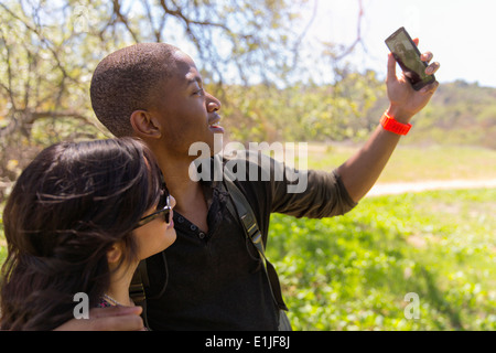Young couple posing for self portrait in park - Stock Photo