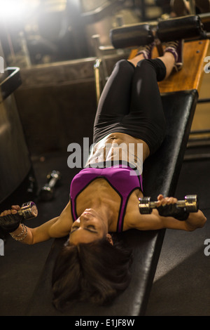 Mid adult woman doing abdominal exercise on weight bench