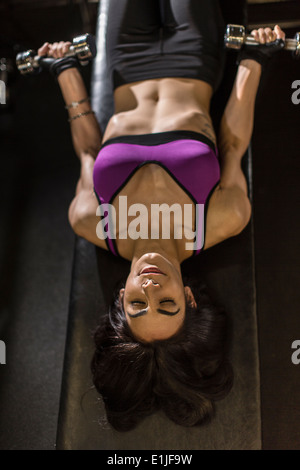 Mid adult woman using dumbbells for abdominal exercise - Stock Photo