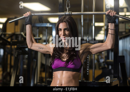 Mid adult woman using bar in gym for pectoral exercise - Stock Photo