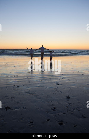 Father and sons walking on beach - Stock Photo