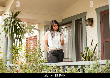 Young woman using smart phone on porch - Stock Photo