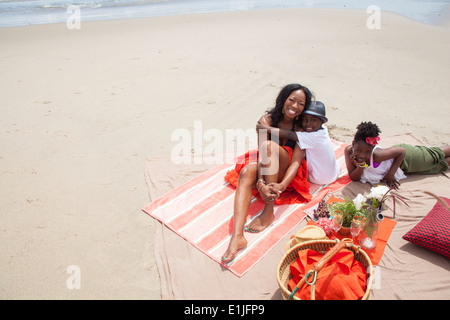 Mother and children relaxing on beach - Stock Photo