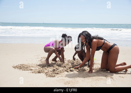 Mother and children digging in sand on beach - Stock Photo