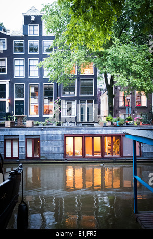 Canal with houseboats in Amsterdam, The Netherlands - Stock Photo