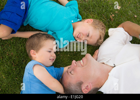 Father and sons playing on grass - Stock Photo
