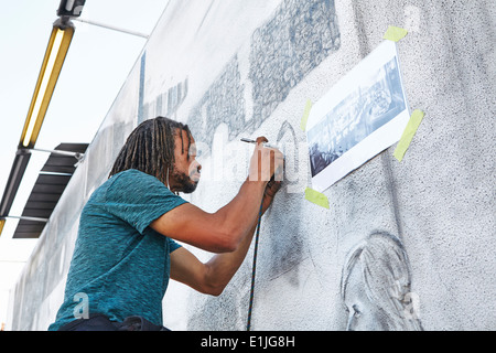 Male african american airbrush artist painting mural - Stock Photo