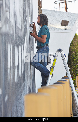 Male african american airbrush artist on step ladders painting mural Stock Photo