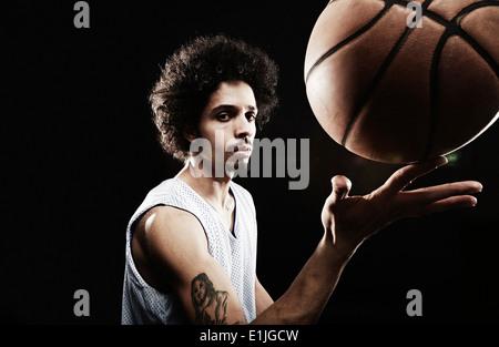 Basketball player balancing basketball on finger - Stock Photo