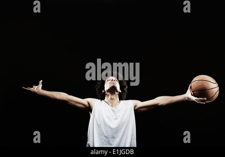 Basketball player holding basketball with arms out - Stock Photo