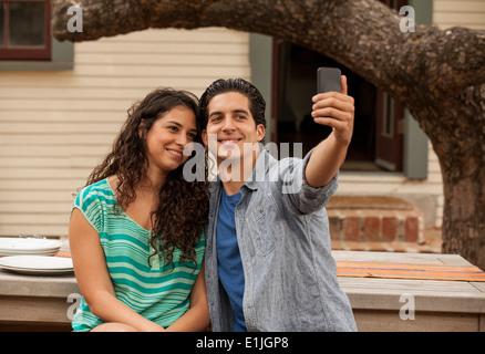 Couple taking self portrait photograph using smartphone - Stock Photo
