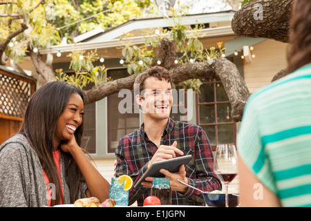 Friends sitting around table sharing barbecue food, man using digital tablet - Stock Photo