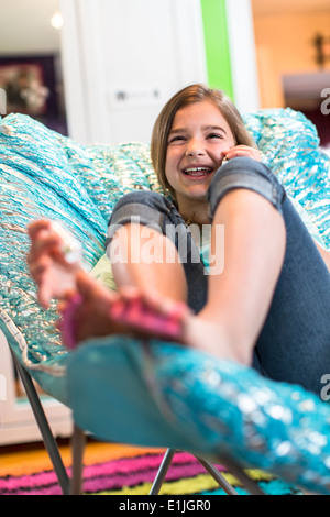 Girl sitting on armchair on phonecall - Stock Photo