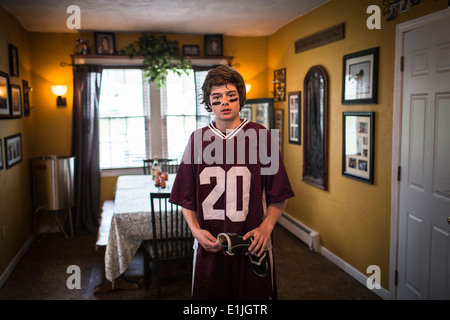 Teenage boy wearing lacrosse uniform, standing in dining room - Stock Photo