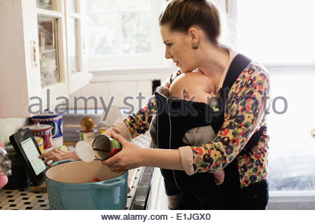 Mid adult mother with baby son in sling preparing food in kitchen - Stock Photo