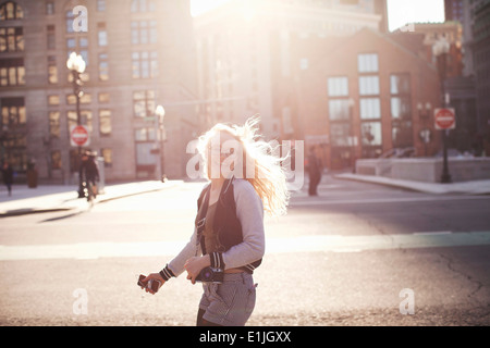 Young woman walking down street in Boston, carrying camera and smartphone - Stock Photo