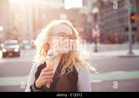 Young woman eating ice cream in street - Stock Photo