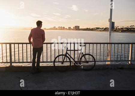 Young man gazing from pier, Long Beach, California, USA - Stock Photo