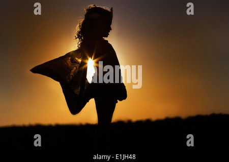 Silhouette of young girl in winged fairy costume at sunset - Stock Photo