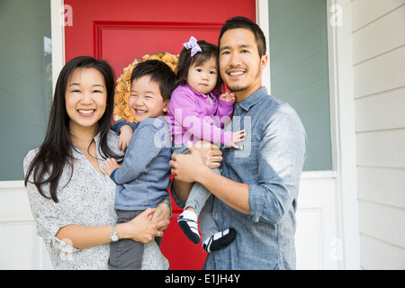 Portrait of mid adult couple and two young children on porch - Stock Photo