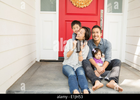 Portrait of mid adult couple with young son and daughter on porch - Stock Photo