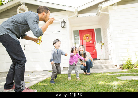 Mid adult couple with two children blowing bubbles - Stock Photo