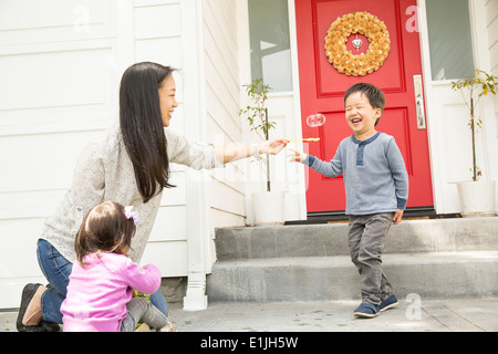 Mid adult woman with young son and daughter making bubbles - Stock Photo
