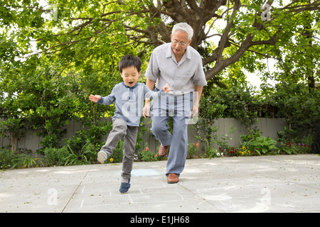 Grandfather playing hopscotch with grandson - Stock Photo
