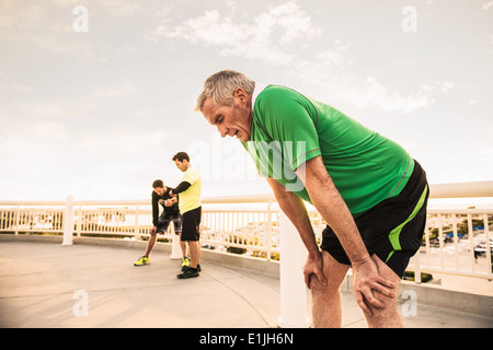 Exhausted male runners taking a break from training - Stock Photo