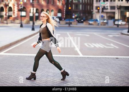 Young woman walking down street - Stock Photo